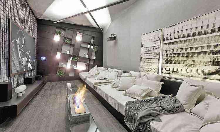 Neste projeto, destaque para o painel de TV com vigas de obra e quatro colchões de solteiro dispostos em cima de um tablado de MDF pintado de preto, fazendo às vezes de sofá - Gustavo Xavier/Divulgação