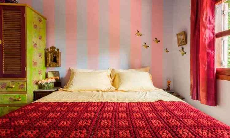 Quarto criado pela designer de interiores Melina Mundim se destaca pela ousadia na parede com listras rosa e azul. Toque contemporâneo ao lado de objetos antigos - Rodrigo Tozzi/Divulgação