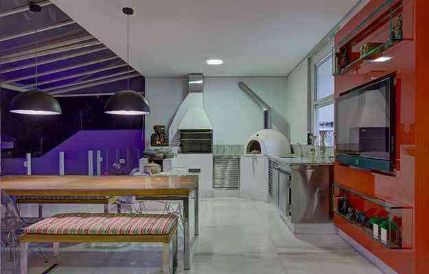 Ambiente gourmet criado pela decoradora Maria Cristina Bahia. O nicho transparente faz as vezes de aparador e não briga com a parede vermelha - Juliana Buli/Divulgação