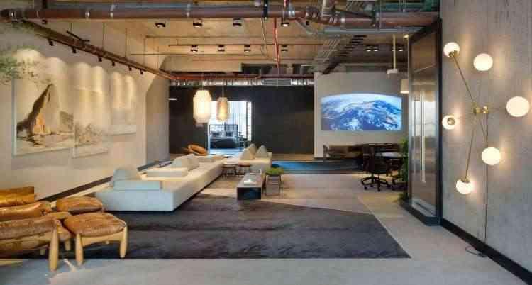 Tanto na parede ao lado quanto no fundo do espaço, os lustres imponentes chamam atenção no ambiente projetado por Laura Santos para mostra de decoração - MCA Studio/Divulgação