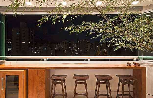A arquiteta Marina Dubal criou uma bancada de madeira com banquetas integradas à adega - Henrique Queiroga/Divulgação