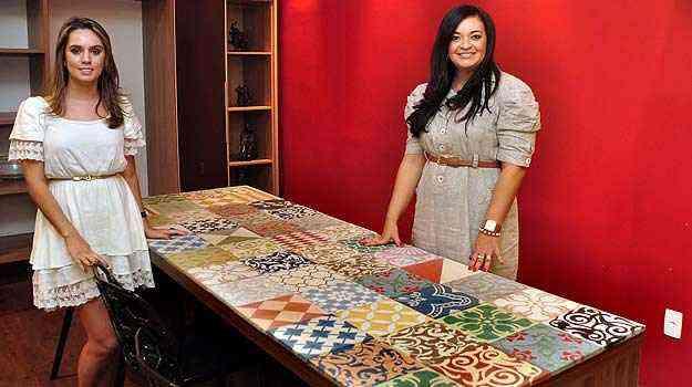 Ívia Maia e Mirlene Saels mostram mesa de madeira de tampo refeito com azulejos antigos - Eduardo de Almeida/RA studio
