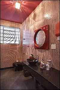 Banheiro feminino - Pastilhas de vidro rosa, louças pretas, espelho e adornos de cerâmica encontrados em brechós - Foto: Jomar Bragança/Divulgação