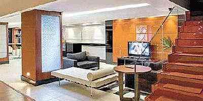 Nesta sala aparece uma tendência: o painel atrás da televisão é feito de aplicações em vidro laqueado laranja e tem as laterais em vidro negro - Clausem Bonifácio/Divulgação
