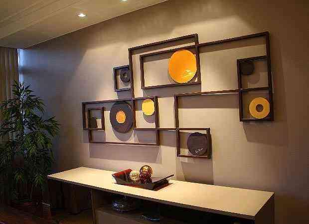Esferas de Murano bronze foram apoiadas em uma base de resina sobre um aparador de laca. A opacidade do móvel contrasta com a leveza da peça decorativa.Os tons do vidro harmonizam com o do aparador e com o da escultura da parede - Divulgação