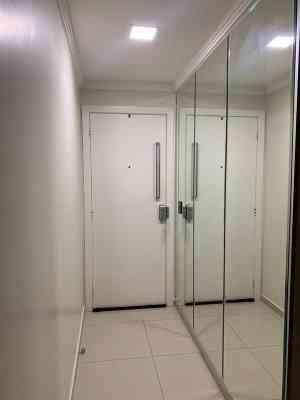 Porta de entrada com fechadura eletrônica intelbrás e espelho moderno.