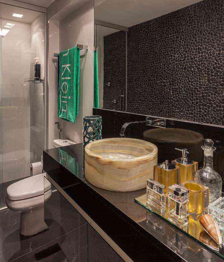 Banheiro possui bela cuba em ônix paquistanês e revestimento de parede seixo negro - Daniel Mansur/Divulgação