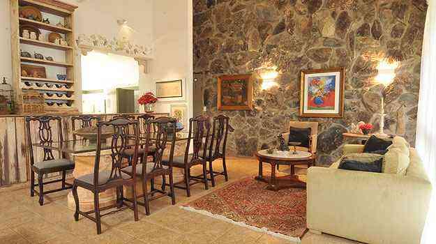 SALA DE JANTAR - Com 5m de pé direito, a sala de jantar tem parede revestida de pedras. A mesa traz tampo e vidro contornado que já funcionou como poste - Marcos Michelin/EM/D.A Press