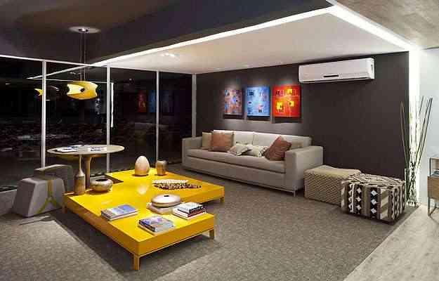 Nesta sala, o amarelo está presente no lustre e na mesa de centro. A arquiteta Heloiza Alcoforado optou por um cômodo bem neutro - as paredes são escuras; o teto, cinza e o destaque fica para os objetos coloridos, que trazem energia ao ambiente - Haruo Mikami / Divulgação