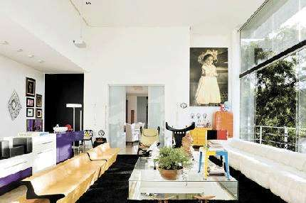 Nesta sala, os móveis coloridos são poucos, mas realçam e complementam a decoração baseada em cores claras. Peças-chave da harmonização do ambiente, a cômoda amarela, o frigobar laranja, o armário roxo e a cadeira multicolorida dão vida ao ambiente moderno. Projeto assinado pelo arquiteto Leo Romano - Leo Romano/Divulgação