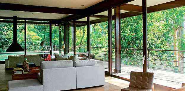 Com 700 m², esta casa em Carapicuíba, SP, aproveita a luz natural com o uso de muito vidro e se integra à natureza do entorno. O projeto é de autoria de Juliana Bertolucci - Divulgação