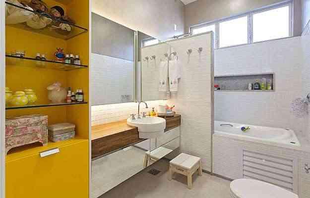 No projeto da arquiteta Marina Dubal, o amarelo da estante é o destaque do banheiro  - Henrique Queiroga/Divulgação