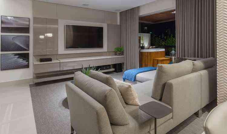 No apartamento para um casal, o painel de TV na sala é um grande armário não aparente, que serve como um ótimo espaço de armazenamento. Projeto de Fabiana Visacro  - Henrique Queiroga/Divulgação