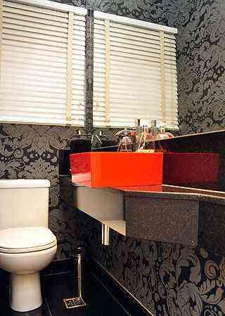 Papel de parede escuro contrasta com a pia laranja: modernidade com um toque clássico - Eduardo Almeida/RA Studio - 30/4/03
