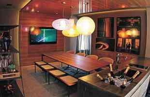 A arquiteta lembra que, atualmente, as pessoas usufruem e ocupam suas casas como um espaço versátil e múltiplo. Assim, o ato de receber os amigos se tornou algo mais despojado, informal. Dessa forma desenvolveu um ambiente constituído de uma grande mesa e seus apoios: uma bancada, um cooktop, uma pia, um bowl de bebidas geladas, uma adega vertical. Móveis de design, iluminação equilibrada, revestimentos rústicos e sofisticados se harmonizam nessa proposta moderna e aconchegante - Ana Carolina Matos