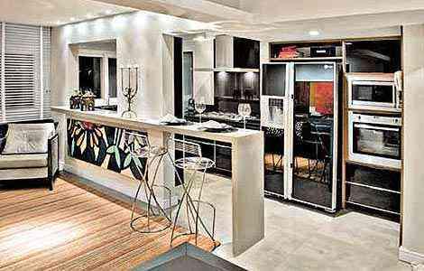 Nesse apartamento, a opção criativa foi colocar o quadro abaixo da bancada que divide sala da cozinha. Projeto dos arquitetos Hélio Albuquerque e Sônia Peres - Divulgação